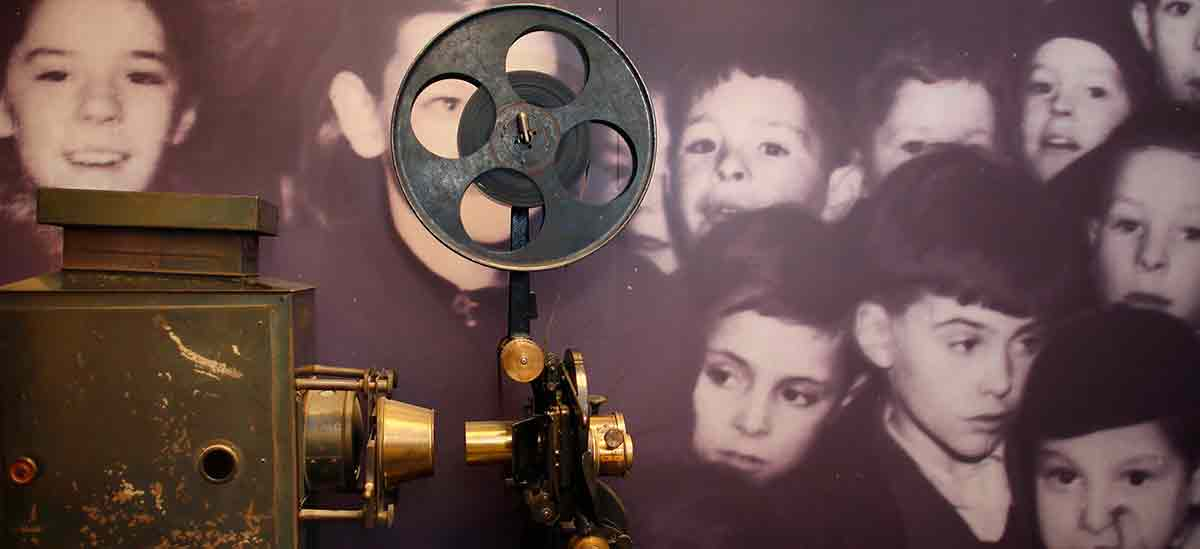 Old cinema reel camera with background photo of children